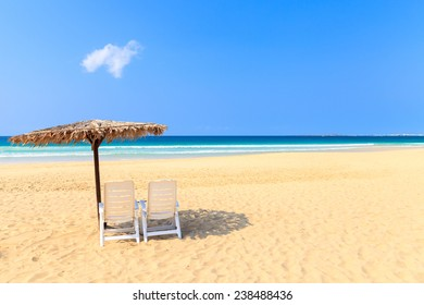 Tropical beach scenery with parasol and deck chairs in Boavista, Cape Verde - Cabo Verde