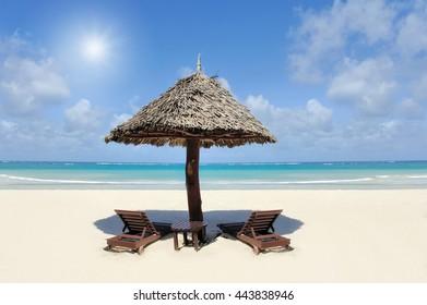 Tropical beach with straw umbrella