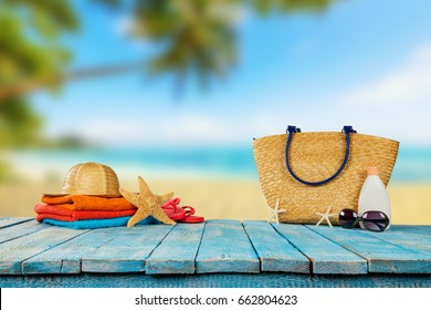 Tropical beach with sunbathing accessories placed on blue wooden planks, summer holiday background. Travel and beach vacation, free space for text.