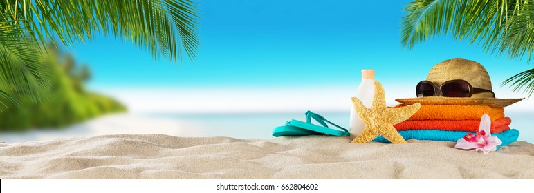 Tropical beach with sunbathing accessories, summer holiday background. Travel and beach vacation, free space for text.