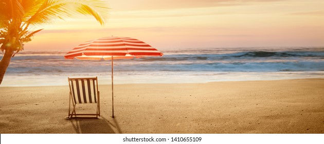 Tropical beach in sunset with beach chair and umbrella
