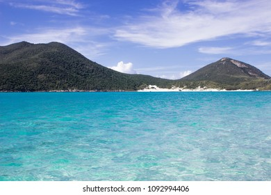 Tropical beach with transparent blue water and mountains in Arraial do Cabo, Brazil.