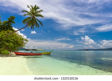 Tropical beach with Two local boats on island coast, coconut palm, white sand and turquoise water, beautiful sky with clouds. Indonesian islands