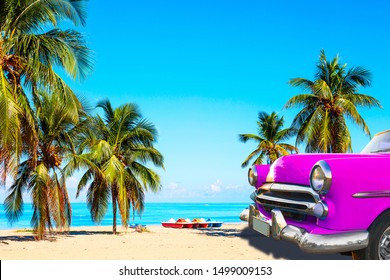 The tropical beach of Varadero in Cuba with american classic pink car, sailboats and palm trees on a summer day with turquoise water. Vacation background.