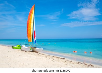 The tropical beach of Varadero in Cuba with a colorful sailboat on a summer day with turquoise water