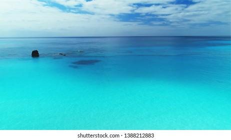 Tropical blue coral ocean sea beach waters and rocks