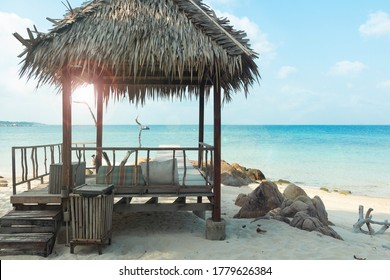 Tropical cabana on the lonely white sand beach with the blue ocean view and sun flare. Relaxing, quite atmosphere on beautiful seashore. Koh Munnork private island, Rayong province, Thailand.