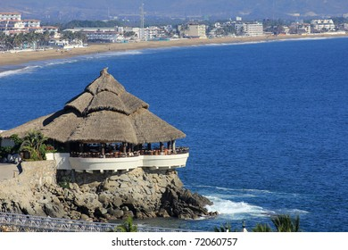 A tropical cabana on a rock jetty by the beach and ocean