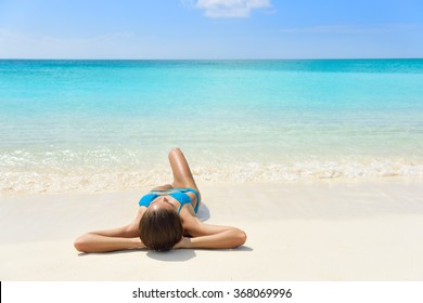 Tropical Caribbean beach vacation - suntan relaxation woman. Bikini girl lying down relaxing on white sand exotic destination sleeping and sunbathing during summer holidays.