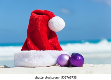 Tropical Christmas Card. Red Santa helper hat with fir tree balls on sandy beach close to Caribbean sea. Tourism and travel vacation concept.