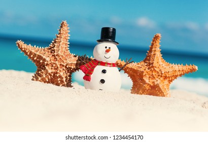 Tropical Christmas greeting card, decorative snowman with star fish on sandy beach, sea view with copy space