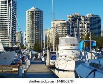 Tropical city waterfront marina/dock with boats in sea water with high rise appartment buildings backdrop. Safe haven for sailing and cruising vessels. Southport, Queensland, Australia.