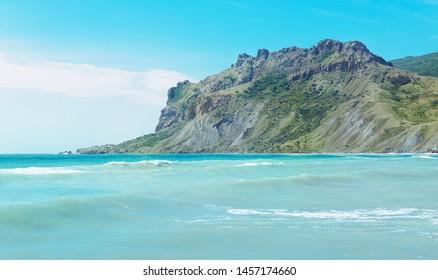 Tropical coast, blue sky, azure sea water and big mountains.