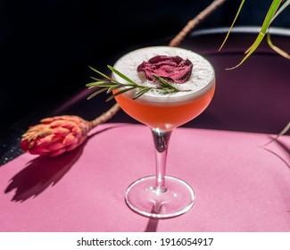 tropischer Cocktail auf Blattwerk-Hintergrund, Schatten von der Sonne. rosafarbener Hintergrund