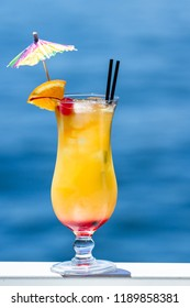 tropical cocktail served outside with a natural blue water background as a travel holiday concept