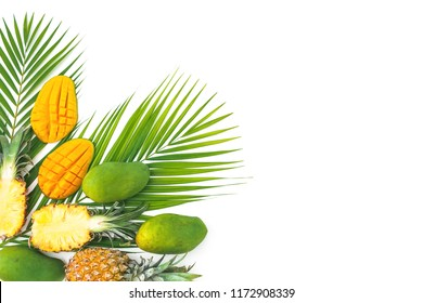 Tropical composition of pineapple and mango fruits with palm leaves on white background. Flat lay, top view. Copy space