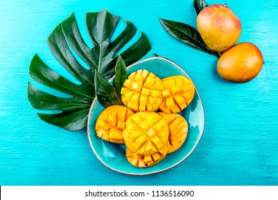 Tropical concept, Tropical leaves and mango on blue background.