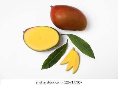 Tropical cut and whole mango with green leaves isolated on white, flat lay