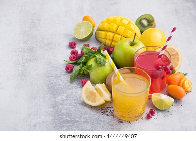 Tropical detox drinks with chia seeds, mango, lemon, raspberry, currant and kumquat fruits on a stone table. freshness exotic summer beverage. Copy space.