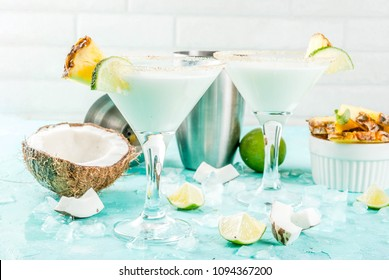 Tropical drink, Frozen Coconut Pineapple Margaritas with frozen pina colada, tequila, pineapple juice and lime,  light blue background, copy space