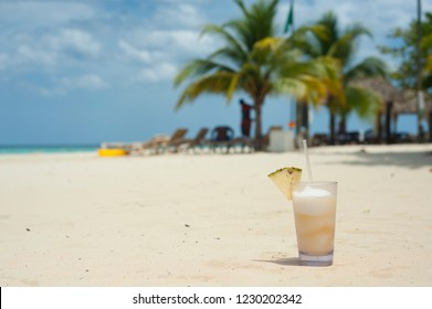 A tropical drink on a tropical beach with palm trees.