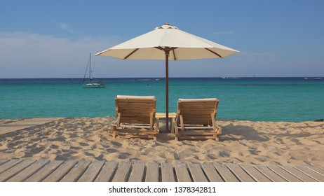 Tropical exotic beach with two empty wooden lounge sunbeds and white umbrella