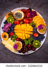 Tropical exotic fruits assorted Mango, Kiwi, Orange, Passion Fruit on a plate, top view