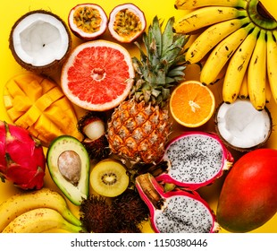 Tropical exotic fruits assorted Pineapple, Coconut, Pitahaya, Kiwi, Banana, Mango, Orange, Avocado, Passion Fruit on yellow background