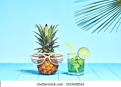 Tropical fashionable Pineapple Hipster with Cocktail on Beach. Bright Summer Color. Trendy fashion Style. Hot summertime Vibes. Creative Art. Fun party fashion Mood. Minimal