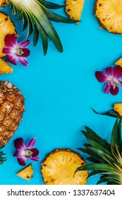 Tropical flatlay of various fruits and flowers on blue