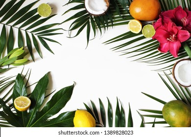 Tropical floral and exotic fruit frame, web banner. Coconut, lemons, mango and amaryllis flowers on lush plam and aralia leaves. White table background. Summer vacation concept. Flat lay, top view.