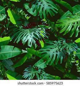 Tropical floral leaves seamless pattern green color on a black jungle background. Natural photo collage green color. Artistic design for floral print and modern wallpaper.