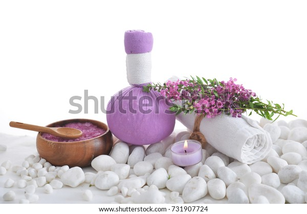 Tropical flower with herbal ball ,towel, salt in bowl ,candle,spoon on pile of white stones