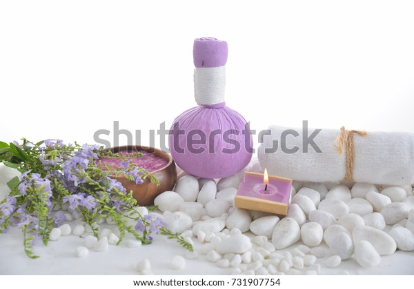 Tropical flower with herbal ball ,towel, salt in bowl ,candle, pile of white stones