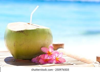 Tropical fresh coconut cocktail decorated plumeria on white beach