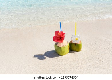 Tropical fresh coconut cocktail on white beach. Two coconut drinks on luxury tropical resort in Maldives island. Fresh drinks on hot summe day, blue sea background.