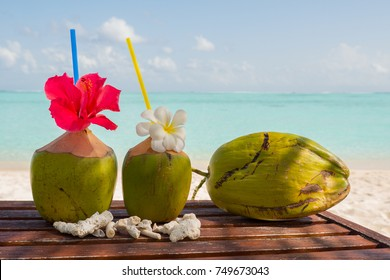 Tropical fresh coconut cocktail on white beach. Two coconut drinks on luxury tropical resort in Maldives island. Fresh green coconut cocktails on sandy Maldives beach with turquoise sea background.