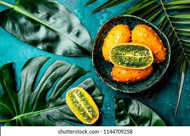 Tropical fruin KIWANO passion fruit in green bowl on turquoise background with tropical palm tree leaves. Top view. Tropical concept.
