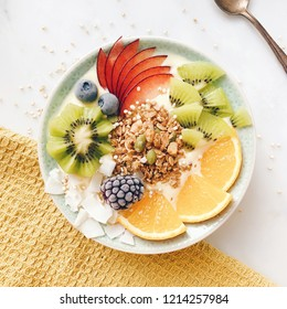 Tropical fruit breakfast bowl with kiwi topview on marble plate