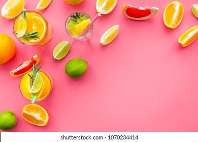 Tropical fruit cocktail with alcohol. Glass with beverage near oranges, grapefruit, lime and rosemary on pink background top view copy space