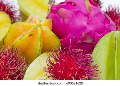 Tropical fruit colorful background group of starfruit dragon fruit and rambutan pink yellow red green on white isolated