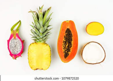 Tropical fruit flat lay with cut pineapple, dragon fruit, papaya, mango, and coconut on a white background