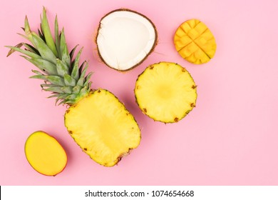 Tropical fruit flat lay with pineapple, mango, and coconut on a pastel pink background. Corner orientation.