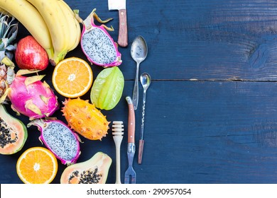 Tropical fruit on black wooden background, top view