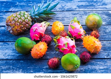 Tropical fruit on the blue old wooden background, top view
