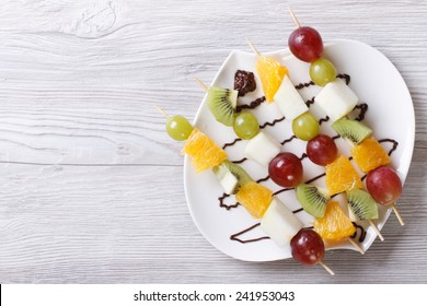 Tropical fruit on skewers with chocolate sauce. horizontal view from above