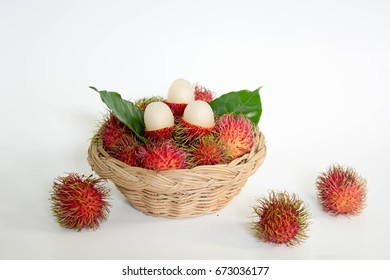 Tropical fruit of rambutan in a basket on white background.  Inside the hairy red skin is white juicy and sweet flesh. It is native to countries in southeast Asia of Indonesia, Malaysia and Thailand.