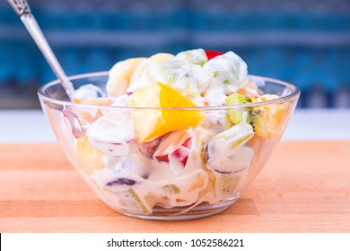 Tropical fruit salad with yoghurt in a glass cup on a wooden table - fruit diet
