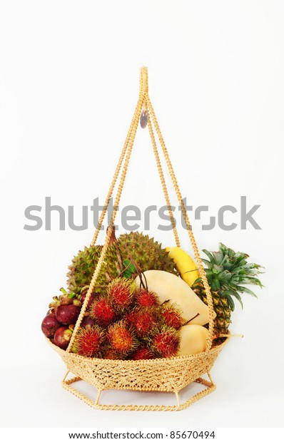 Tropical fruit in Thai style basket, isolated over white background.