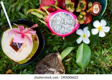 tropical fruits of Asia region Thailand on grass, coconut, mangosteen, dragon fruit, papaya, longan, rambutan and flowers